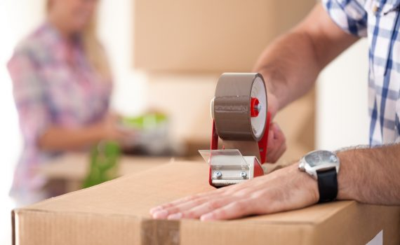 Close up of male hand packing cardboard box, concept moving house